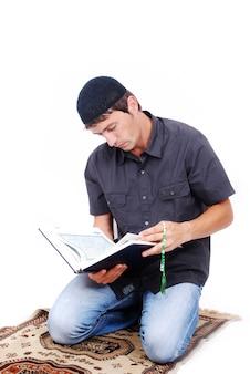 O homem muçulmano está segurando o livro de azevinho qoran e rezando na traditiona