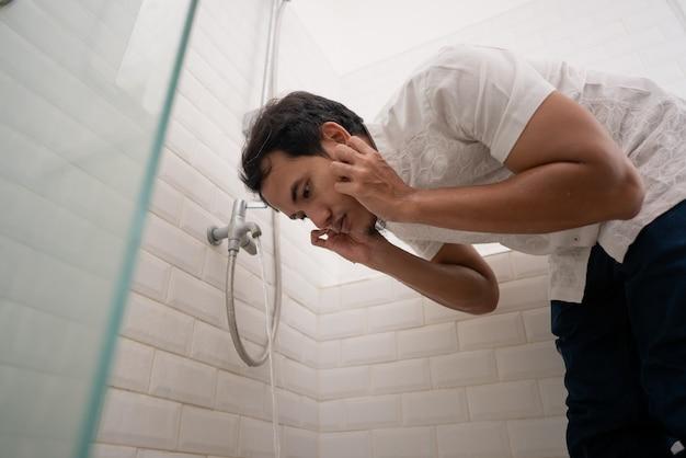 O homem muçulmano limpa seu corpo com água da torneira antes de orar. limpeza de ablução wudhu