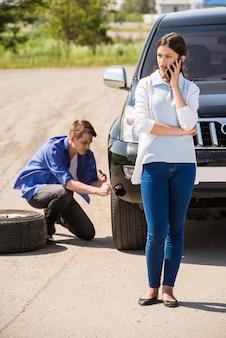 O homem muda a roda no carro e a garota liga.