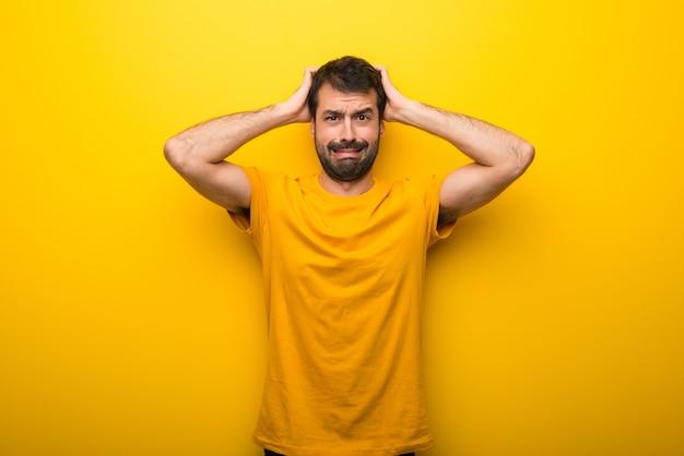 O homem na cor amarela vibrante isolada toma as mãos na cabeça porque tem a enxaqueca
