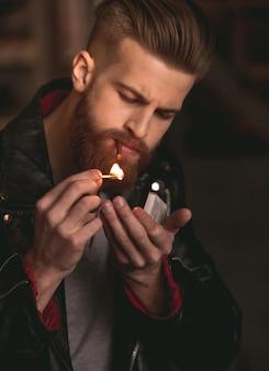 O homem na jaqueta de couro está acendendo um cigarro.