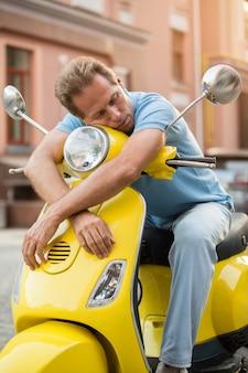 O homem na scooter está dormindo.