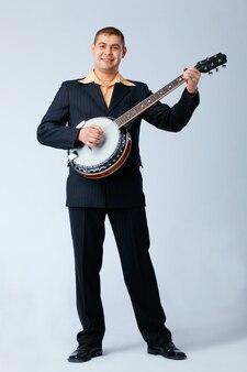 O homem na suíte está de pé e tocando banjo contra o branco,