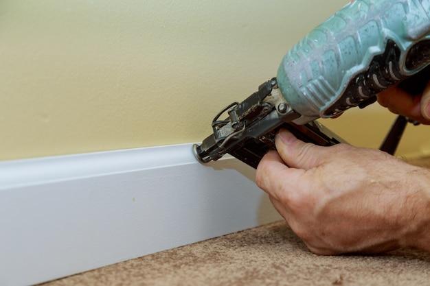 O homem nailer do revestimento do calibre do ar da guarnição do molde baixo pregou o contratante de construção feito sob encomenda da casa
