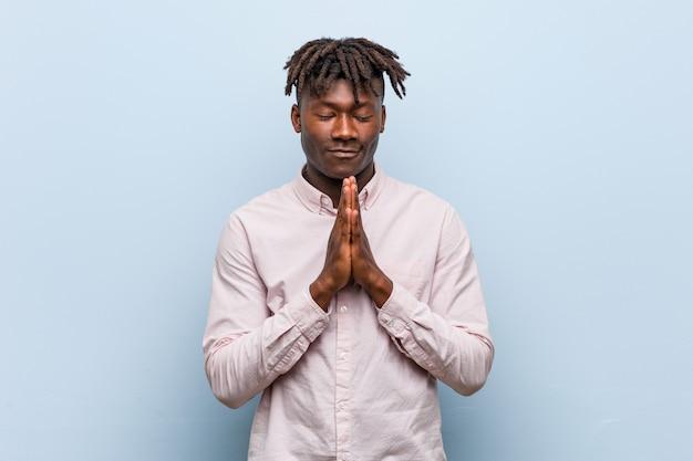 O homem negro africano novo do negócio que guarda as mãos reza perto da boca, sente-se confiante.