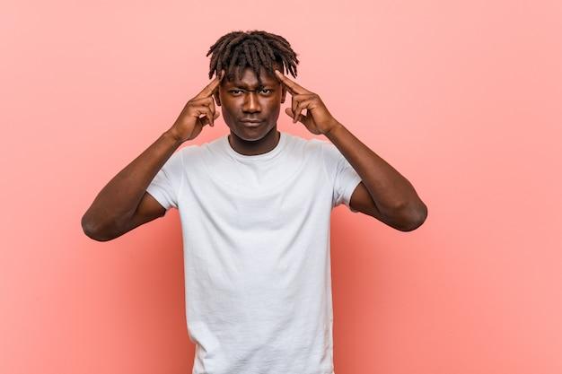 O homem negro africano novo focalizou em uma tarefa, mantendo os dedos indicadores que apontam a cabeça.