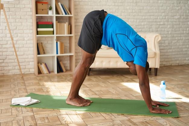 O homem negro atlético faz a ioga avançada na esteira em casa.