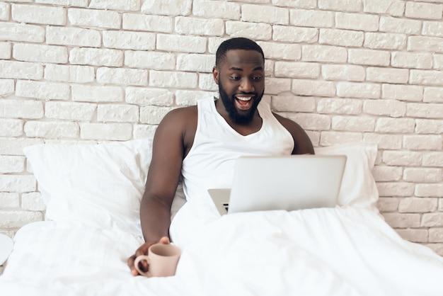 O homem negro bebe o café na cama ao trabalhar com o portátil.