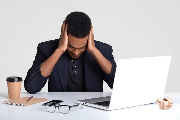 O homem negro deprimido mantém o olhar baixo, mantém as duas mãos na cabeça, não pode continuar trabalhando, tem problemas com os negócios, trabalha com aparelhos eletrônicos modernos, escreve registros no bloco de notas com lápis.