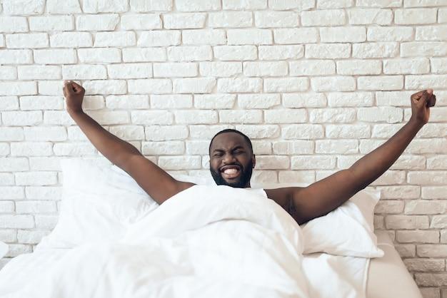 O homem negro e acordado está estendido na cama.