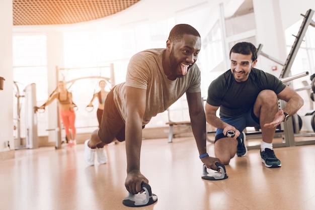 O homem negro mostra a língua e torceu para fora no gym.
