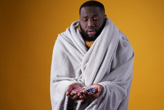 O homem negro tem frio, segurando comprimidos nas mãos.