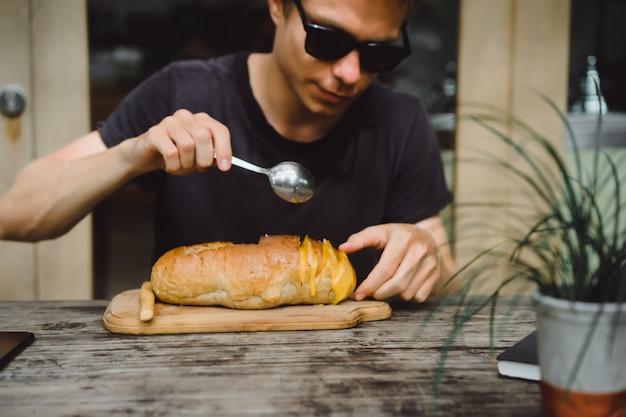 O homem no café tem sopa em um prato de pão.