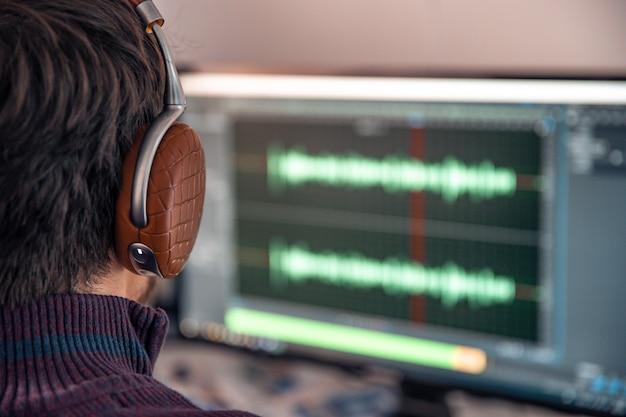 O homem no estúdio de fotografia grava e modifica canto, voz e música para uso comercial. funciona em um editor de áudio em um computador com fone de ouvido