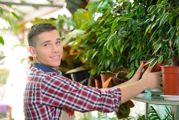 O homem no jardim cuida de flores.