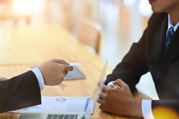O homem no terno dá o cartão telefônico vazio ao tiro do close up do visitante.