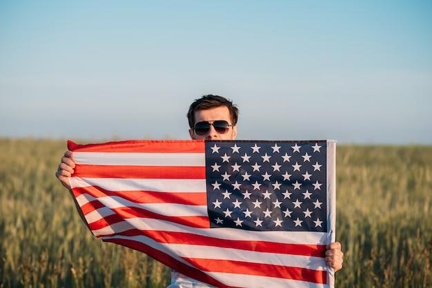 O homem nos óculos de sol guarda a bandeira americana no campo. símbolo do dia da independência, quatro de julho nos eua