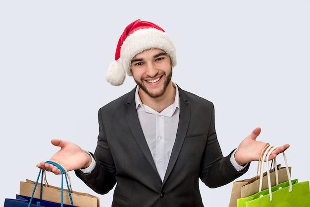 O homem novo alegre e positivo sorri na câmera. ele usa chapéu de natal e terno preto. jovem tem sacolas de compras em ambas as mãos.