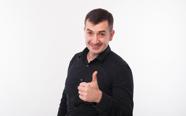 O homem novo alegre na camisa preta está sorrindo e aparecendo o polegar em um fundo branco.