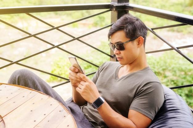 O homem novo asiático desgasta uns óculos de sol e usa um smartphone.