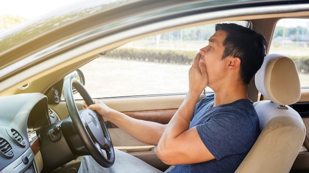 O homem novo asiático que conduz um carro e sente sonolento.