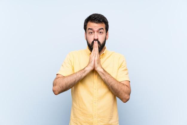 O homem novo com barba sobre a parede azul isolada mantém a palma unida. pessoa pede algo
