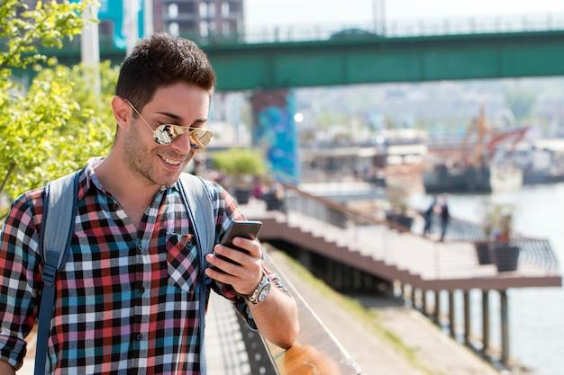 O homem novo considerável aprecia um telefone móvel que senta-se nas escadas.