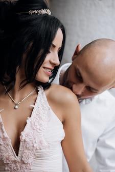 O homem novo considerável da cabeça calva abraça com a morena nova da paixão no vestido de noite cor-de-rosa