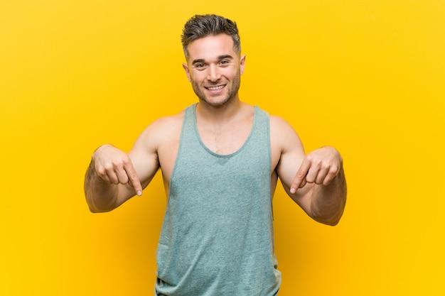 O homem novo da aptidão contra o amarelo aponta para baixo com os dedos, sentimento positivo.