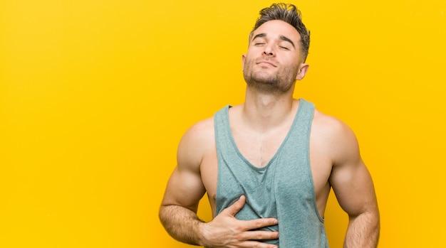 O homem novo da aptidão contra uma parede amarela toca a barriga, sorri delicadamente