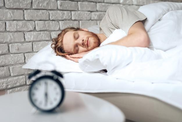 O homem novo de cabelo vermelho dorme no quarto perto do despertador.