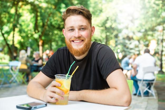 O homem novo de sorriso do ruivo à moda com uma barba bebe um refresco no café.