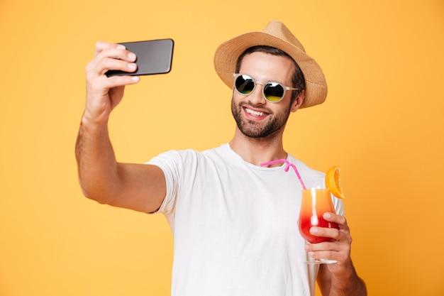 O homem novo de sorriso faz o selfie pelo telefone que guarda o cocktail.