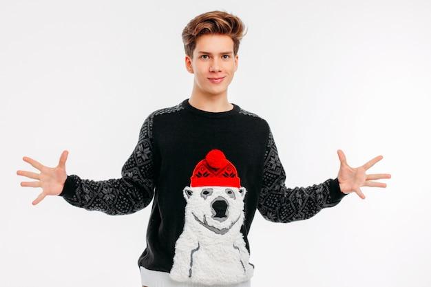 O homem novo de sorriso na camisola acolhedor do urso abraça no fundo branco