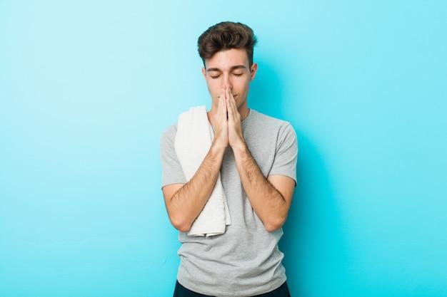 O homem novo do adolescente da aptidão que guarda as mãos reza perto da boca, sente-se confiante.