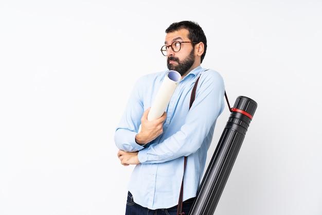 O homem novo do arquiteto com barba sobre a parede branca isolada que faz dúvidas gesticula ao levantar os ombros