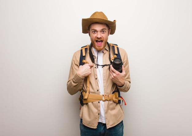 O homem novo do explorador do ruivo surpreendeu, sente bem sucedido e próspero. segurando uma câmera.