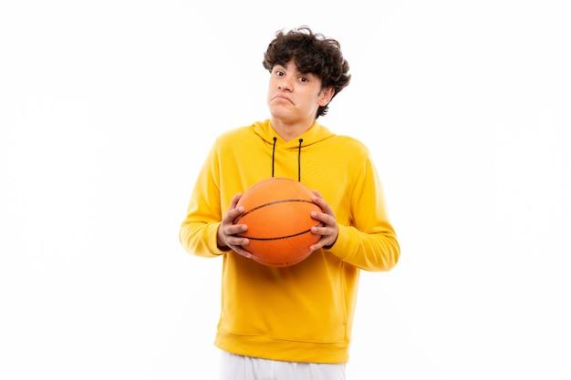 O homem novo do jogador de basquetebol sobre a parede branca isolada que faz dúvidas gesticula ao levantar os ombros