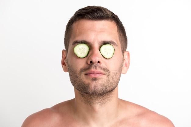O homem novo do restolho cobriu seus olhos com a fatia do pepino que está de encontro ao fundo branco