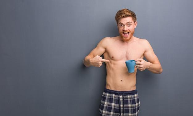 O homem novo do ruivo descamisado surpreendido, sente bem sucedido e próspero. ele está segurando uma caneca de café.