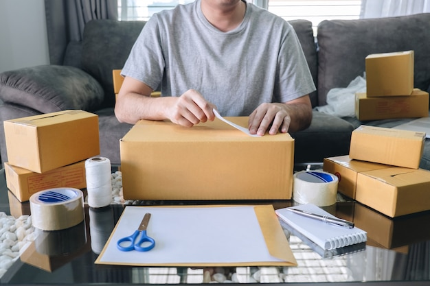 O homem novo do sme do empreendedor recebe o cliente do pedido e o trabalho com empacotamento classifica o mercado em linha da entrega da caixa