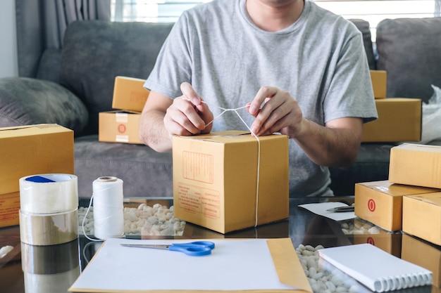 O homem novo do sme do empresário recebe o cliente do pedido e o trabalho com empacotamento classifica o mercado em linha da entrega da caixa no pedido de compra