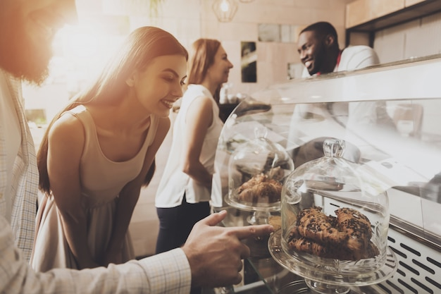 O homem novo e a mulher escolhem pastelarias em um café