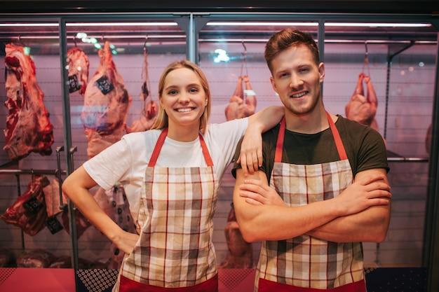 O homem novo e a mulher estão na prateleira de carne na mercearia.