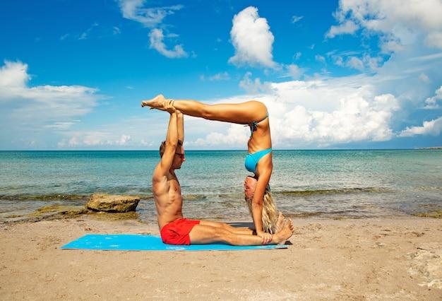 O homem novo e a mulher na praia que fazem a ioga da aptidão exercitam junto. elemento acroyoga para força e equilíbrio