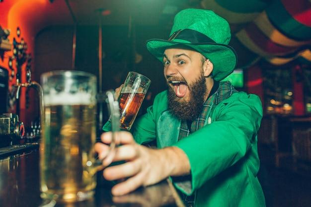 O homem novo entusiasmado feliz no terno verde de st patrick senta-se no balcão da barra no bar. ele bebe cerveja de uma caneca e alcança outra.