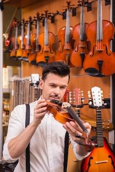 O homem novo está considerando o violino em uma loja da música.