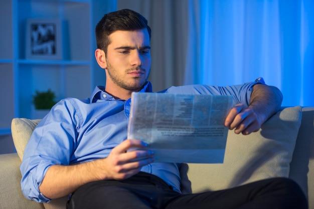 O homem novo está lendo um jornal em casa.