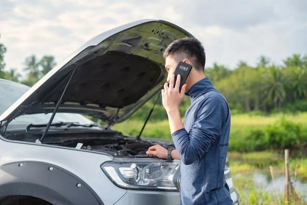 O homem novo faz uma ligação durante o carro quebrado. o homem precisa de ajuda.