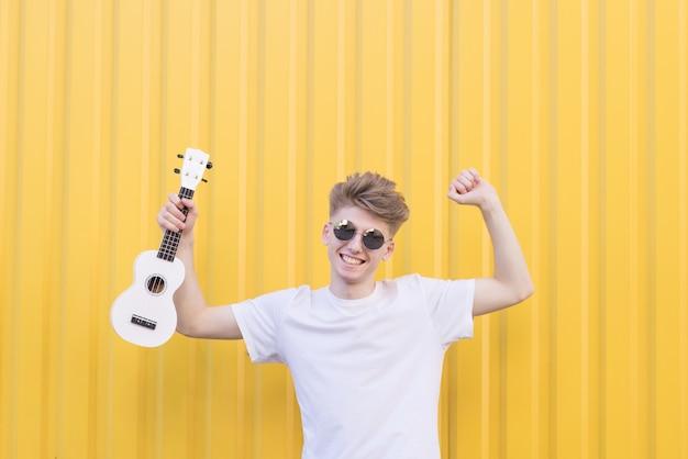 O homem novo feliz com a uquelele em suas mãos levanta contra a parede amarela. conceito musical